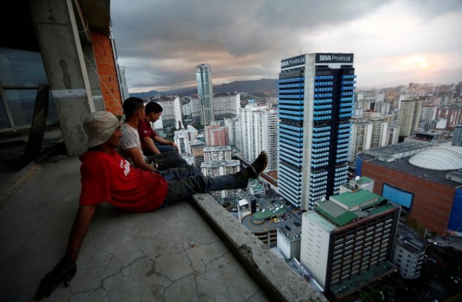 Men rest after salvaging metal on the 30th floor. REUTERS/Jorge Silva