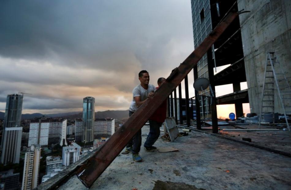 Men salvage metal on the 30th floor. REUTERS/Jorge Silva