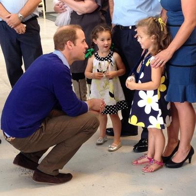 Prince William asks a young girl how she broke her arm.