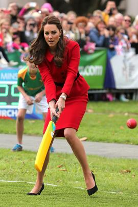 Catherine, Duchess of Cambridge plays a game of cricket during a visit to Latimer Square in...