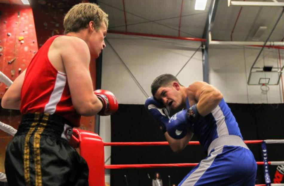 Queenstown light heavyweight Callum Owen (blue) on his way to beating Mitch Lucas, of Hamilton.