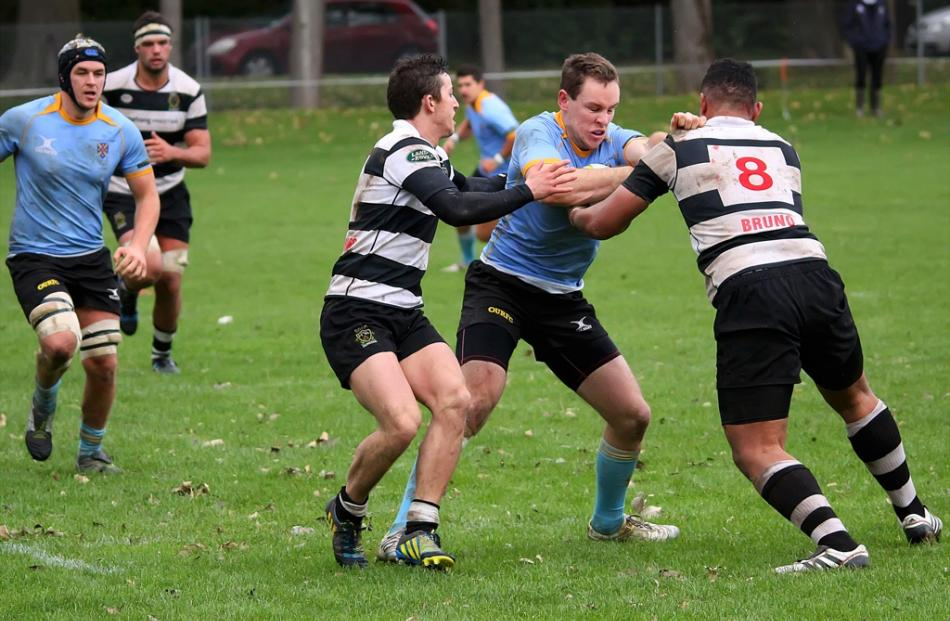 Sam McLachlan for University A drives into Southern defenders Lafaele Faamoe and Josh Walden...