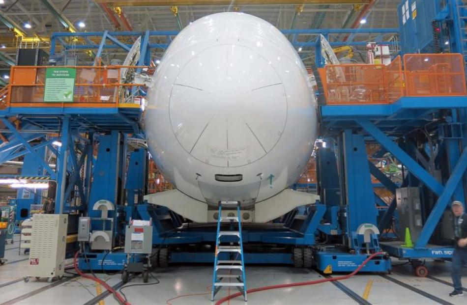 Teams of engineers work in their mobile ''office'' on the Dreamliner production line. Photo by...