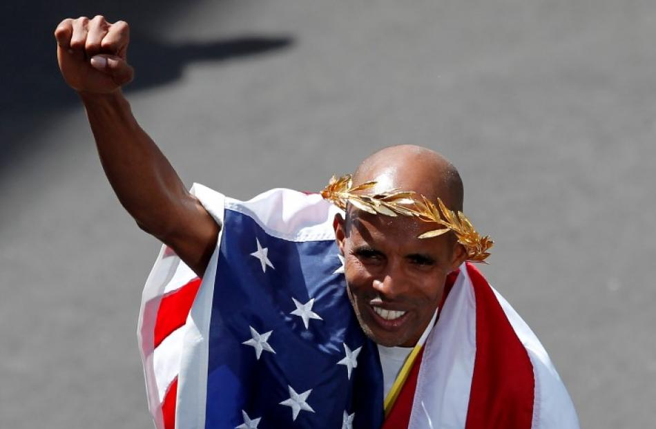 Meb Keflezighi celebrates at the finish line after winning the men's division of the 2014 Boston...