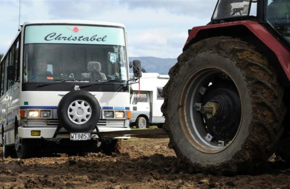 Motorhomes are towed out of the Taieri A&P Showgrounds  on Monday  after becoming bogged down in...