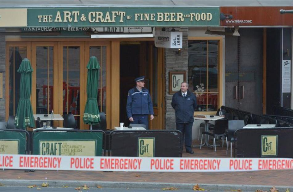 A police officer and a security officer stand outside a cordoned-off Craft Bar in the Octagon...