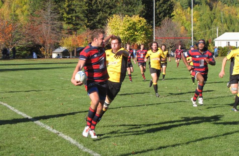 Arrowtown's Gareth Jones swats away an Upper Clutha A player at Jack Reid Park on Saturday.