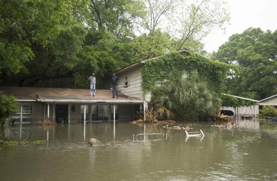 Residents wait for help after flooding in the Kelly Ave. Basin area of Pensacola, Florida. Photo...