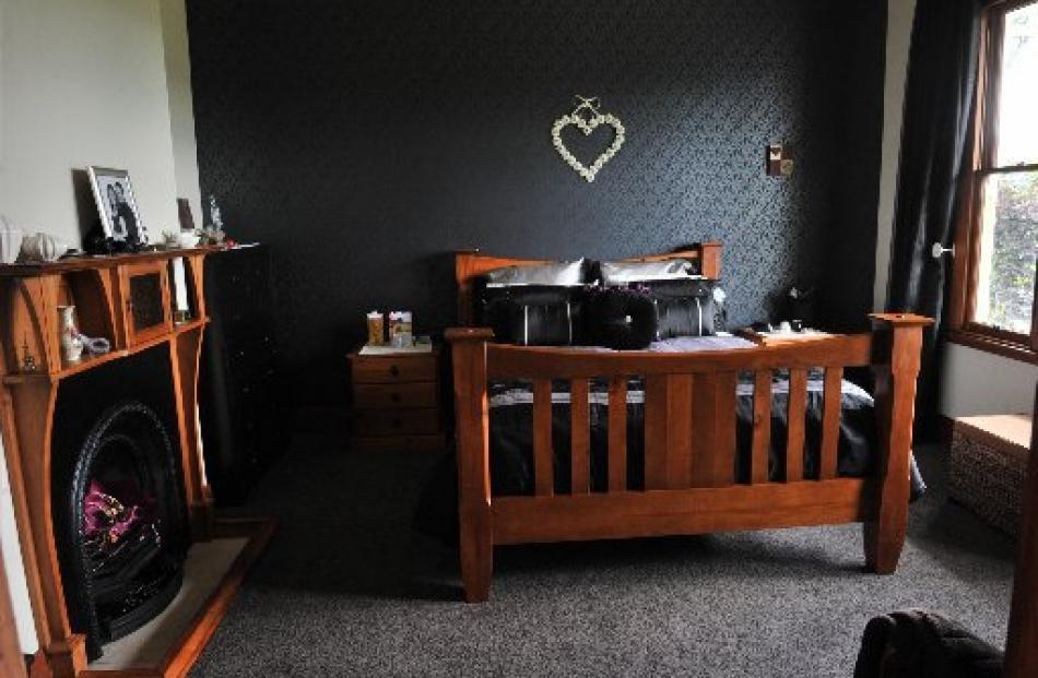 An original fireplace remains in the main bedroom. The dark wallpaper on the feature wall is a...