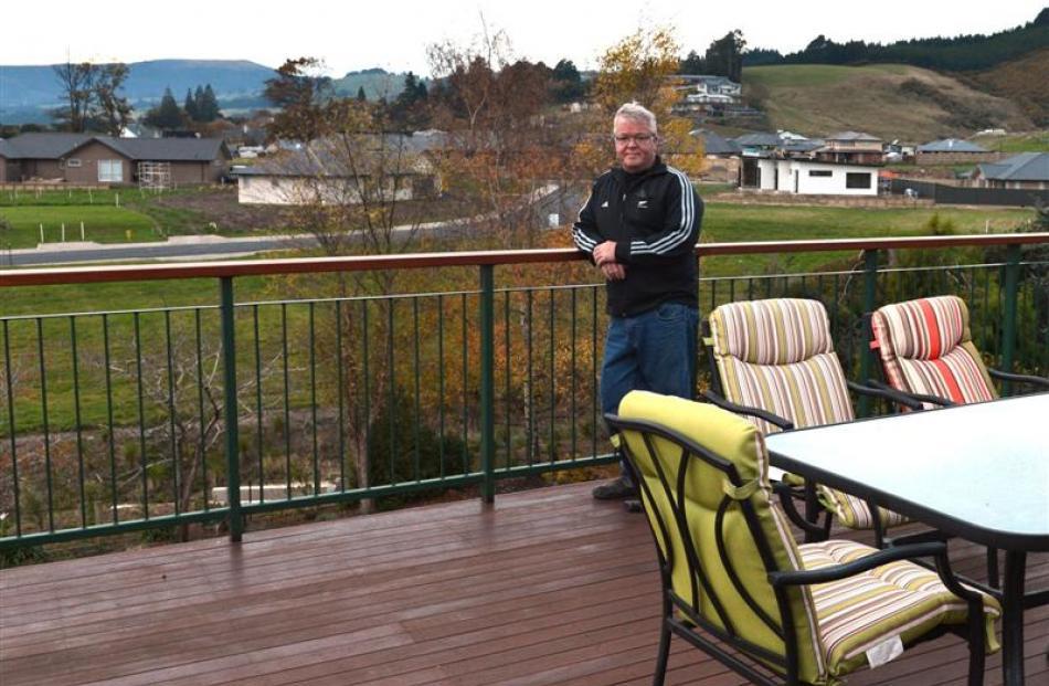 Mr Elliott stands on his suburban deck.