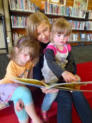 Miriam Geard reads to Charlotte Pomeroy (2) and sister Sophie (4).