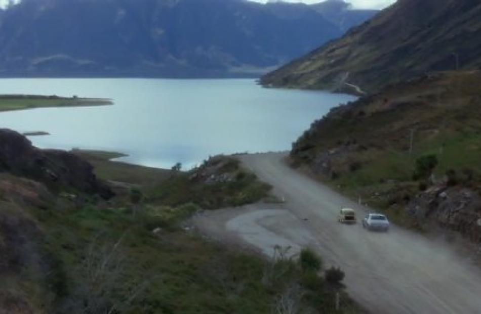 Goodbye Pork Pie, the police car chases the Mini on State Highway 6 at the Neck, with Lake Hawea...