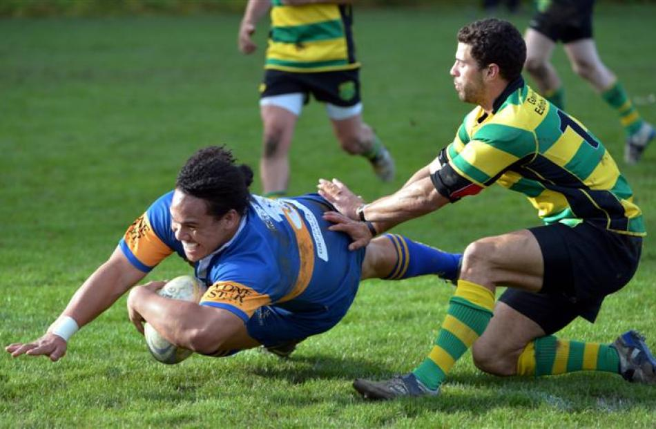 Taieri prop Aki Seiuli beams as he dives past Green Island wing James Spooner to score.