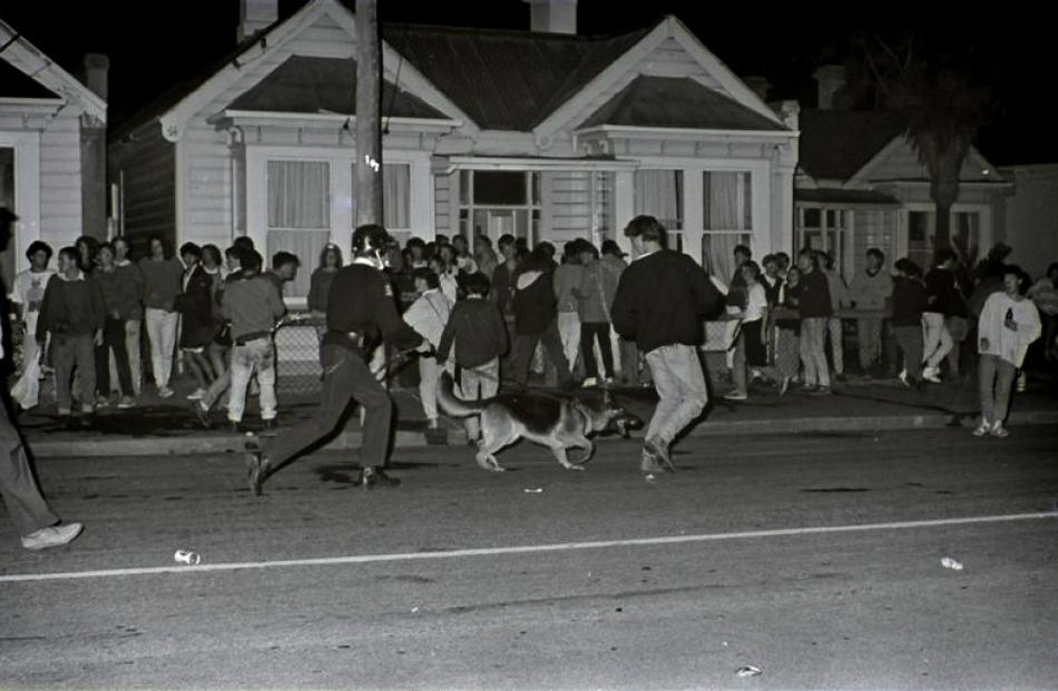 Mr Hanlin and dog clear the street during student unrest in April 1990. Photo by NZ Police.