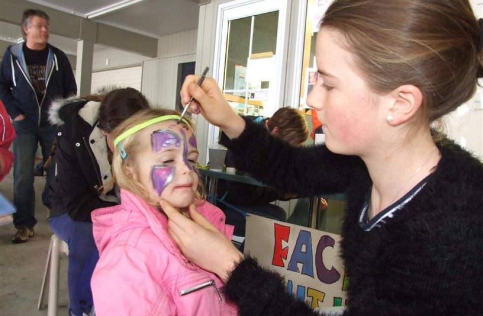 Tahlia Wheeler (5) has her face painted by Elise Streat (14).  Both are from Queenstown. Photos...