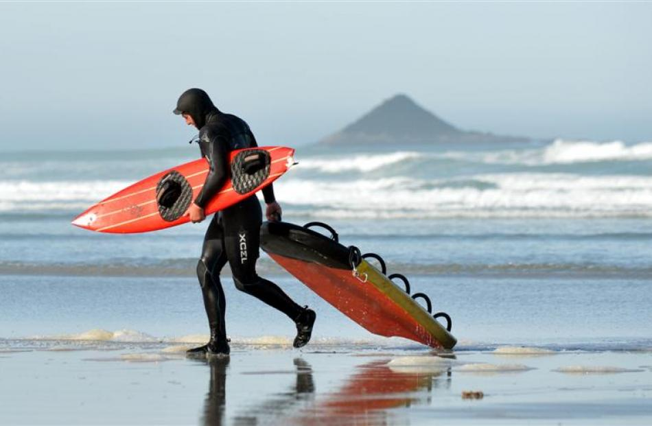 Surfer Dan Smith, of Christchurch, hauls in some of the group's gear after it was taken to shore...