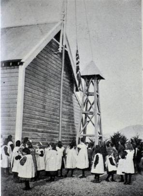 Wylies Crossing School pupils hoist the flag at an earlier building. Photo from Otago Witness,...