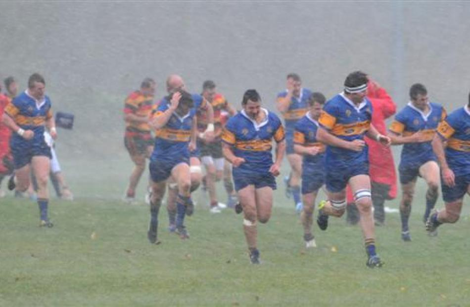 Premier rugby players from Taieri and Zingari-Richmond run for shelter after their game was...