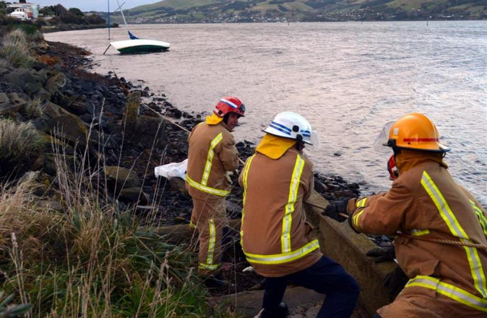 Ravensbourne volunteer firefighters help secure a yacht forced on its side in the high winds on...