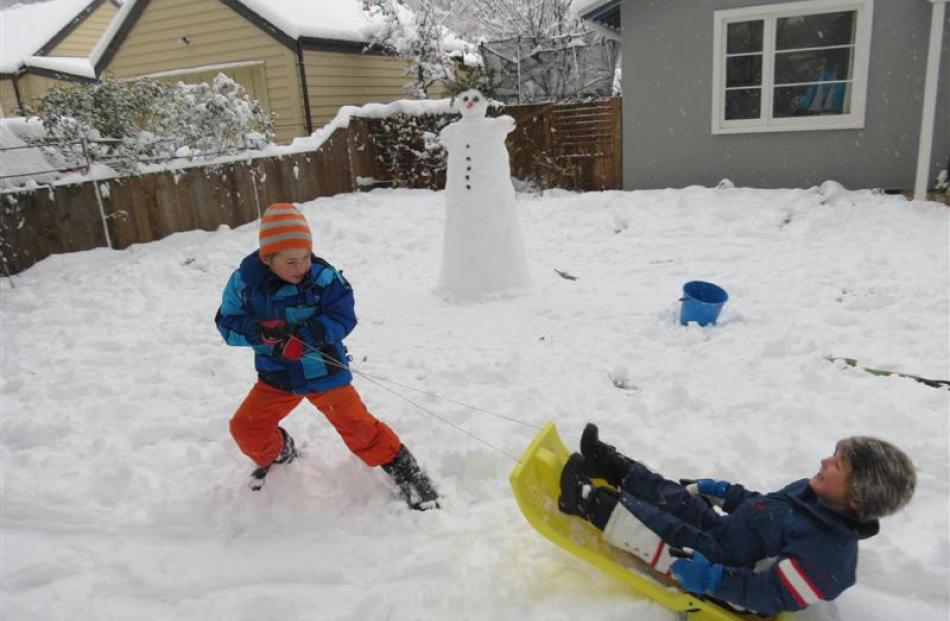 Austin Tyler (6) pulls his little brother Leo (4) on a sled in their front lawn in Arrowtown...