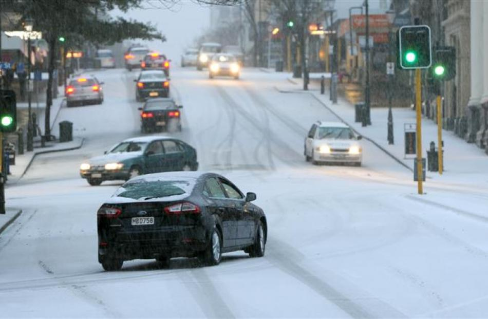 Cars negotiate Princes St near the Exchange in Dunedin yesterday.