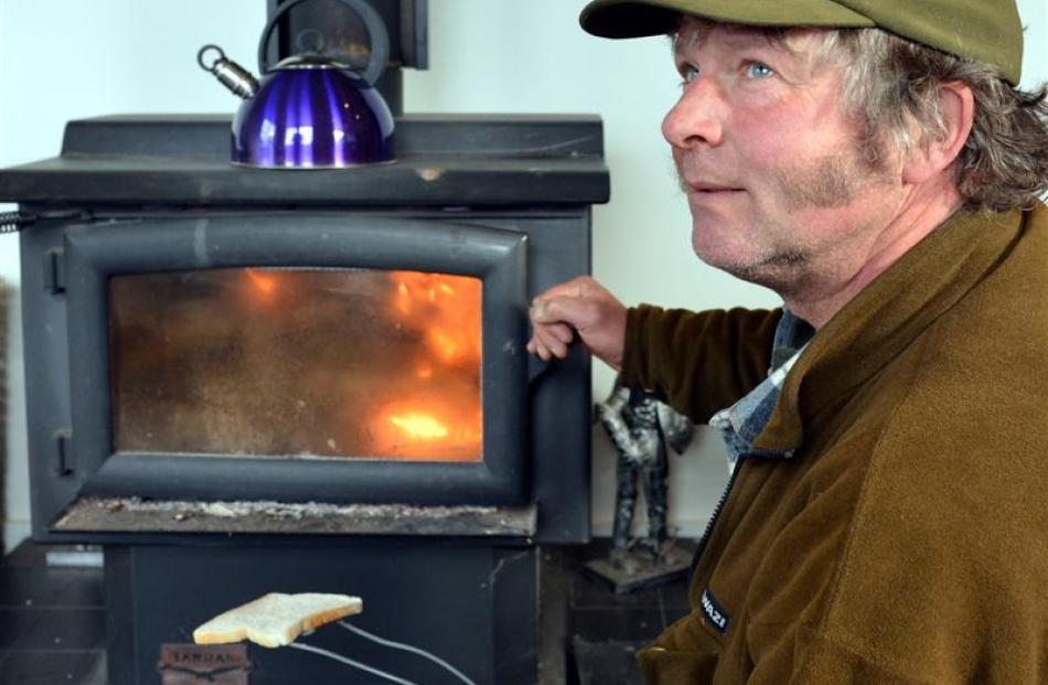 David McKay cooks toast on his log burner at his Cape Saunders home after strong winds knocked...