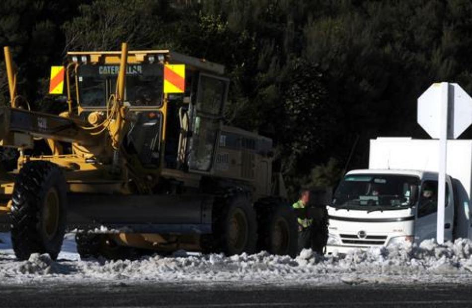 A snow grader tows an Otago Corrections Facility van in Leith Valley Rd yesterday.