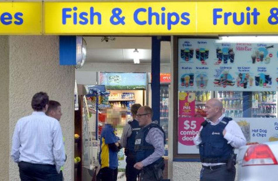 Police at the scene of the Mornington Night 'n Day following an aggravated robbery yesterday. ...