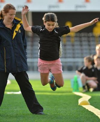 Teariki Tremain (10), of Waikouaiti School, is watched by Sports Otago active movement adviser...