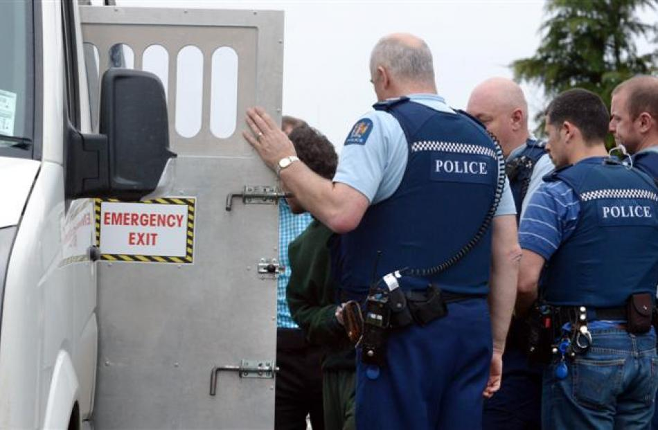 Police surround escapee Maddren as he is herded into a prison van in Milton