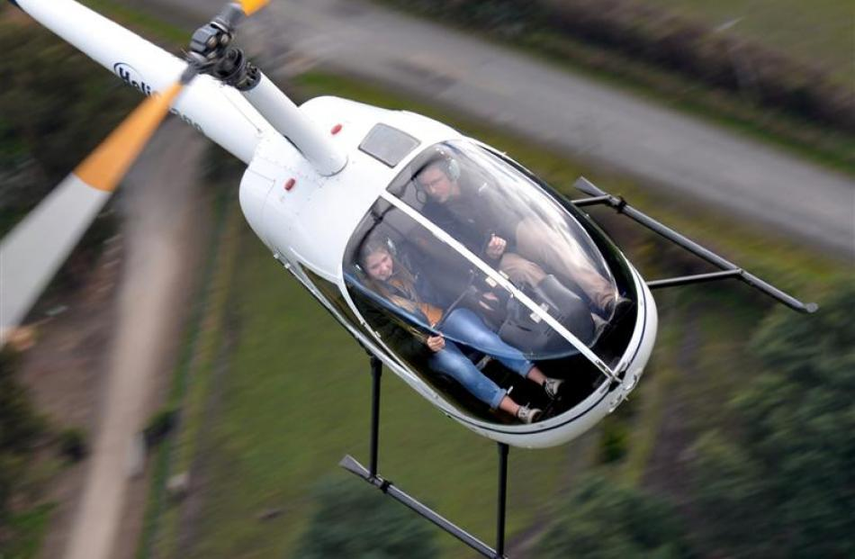 Helicopter pilot Aaron Whitley helps birthday girl Jade MacMillan (15), who was born in a...