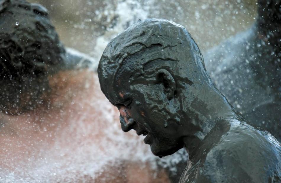 A participant has a shower after a handball match at the Mud Olympics. REUTERS/Morris Mac Matzen