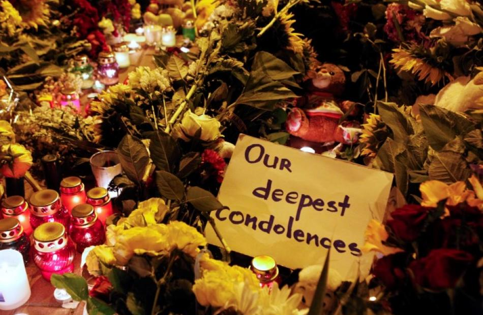 A message of condolence is left among candles and flowers near the Dutch embassy in Kiev. REUTERS...
