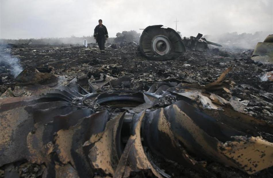 An Emergencies Ministry member inspects the site of a Malaysia Airlines Boeing 777 plane crash,...