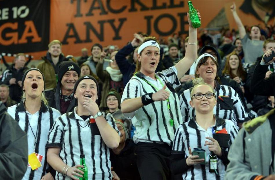 Shinay Archer (holding up bottle), of Dunedin, and friends get into the spirit.