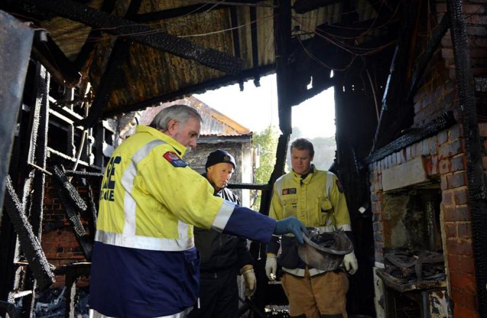 Invercargill fire safety officer Mike Cahill (left) investigates the charred remains of the...