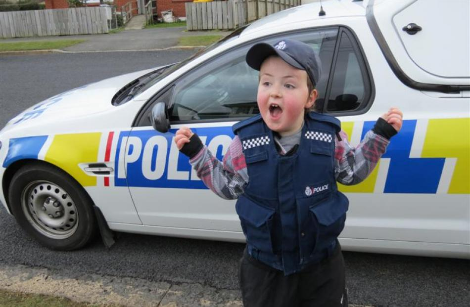 An excited Harley wears a police vest and cap.
