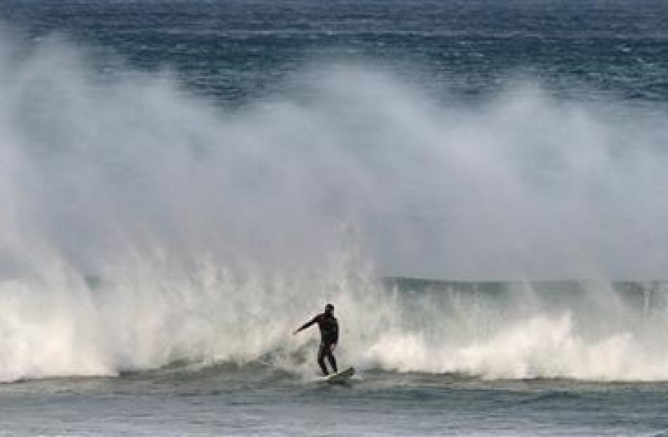 A surfer rides a wave at St Clair while the wind whips up spray as it breaks. Photo by Stephen...