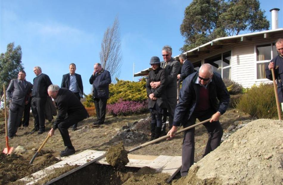 Mourners help fill the grave of Catholic priest Fr Brian Fenton  at his home in Wanaka yesterday....