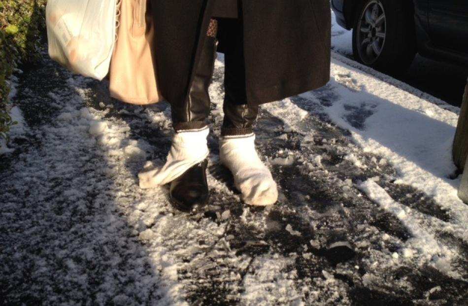 A pedestrian wears socks over shoes to aid traction in the slippery conditions on High St. Photo...