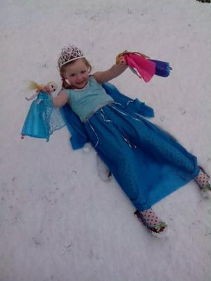 "Queen Elsa (aka Annabelle Tocher) lies in the snow singing ""Let it go, let it go"" from her..."