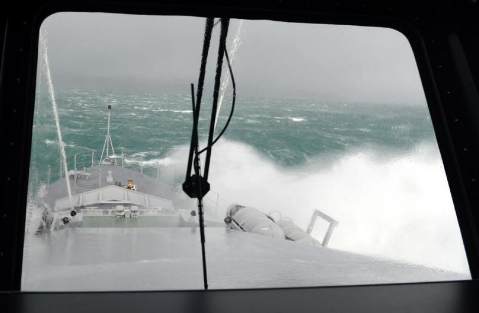 Waves break over the bow.