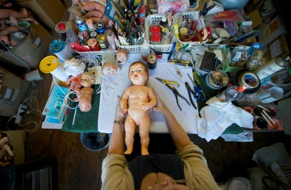 Kerry Stuart, a 25-year veteran at the hospital, repairs a doll on her workbench.