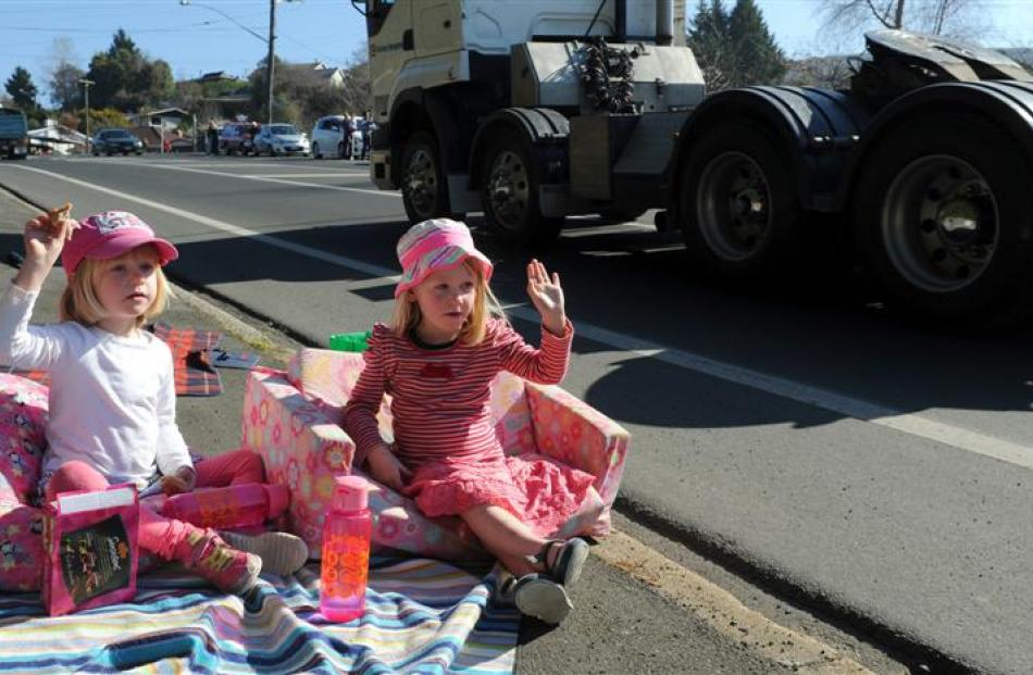 Twins (left) Marlie and Ruby Chisholm (4) wave as the Special Rigs for Special Kids convoy passes...