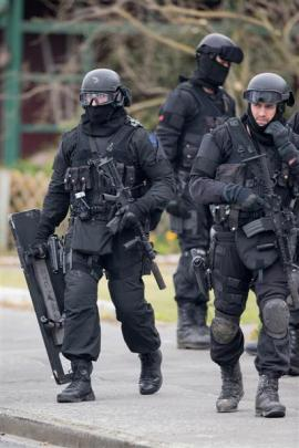 AOS members leave an Ashburton house they have just searched. Photo by NZ Herald.