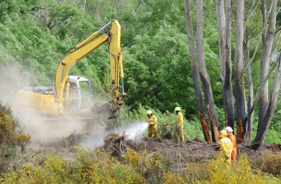Fire crews and a digger operator working to douse the Ettrick fire in scrub along the Clutha...