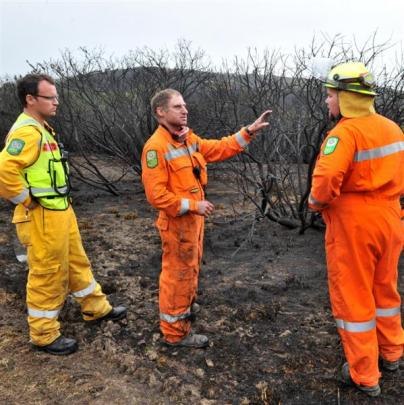 Firefighters (from left) Mort Shepherd, Trevor Booth and Dan Fallow discuss the vegetation fire...