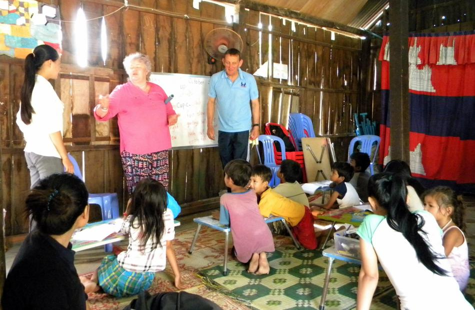 Joan Hasler and Peter Buxton teach Cambodian pupils.