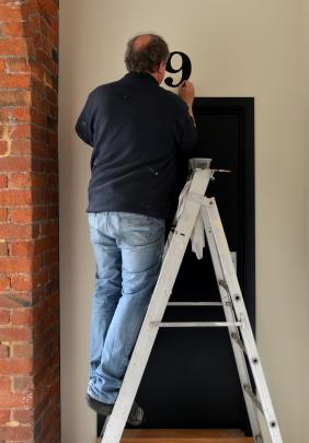 A workman paints a number over the door of an apartment in the same font as that used on the...
