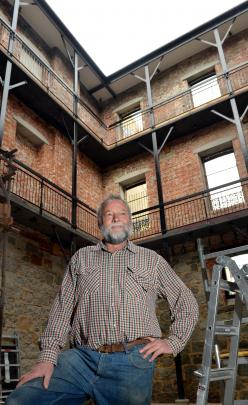 Bruce Purvis stands in the internal full-height atrium that acts as a diaphragm for the building.